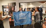 Gedeputeerde Cees Bijl laat na de toekenning van de werelderfgoedstatus trots de Unesco-vlag zien aan de zaal in Museum de Proefkolonie in Frederiksoord.  Foto: DvhN