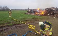 De brandweer blust de afvalhoop bij de ijsbaan in Wanneperveen.