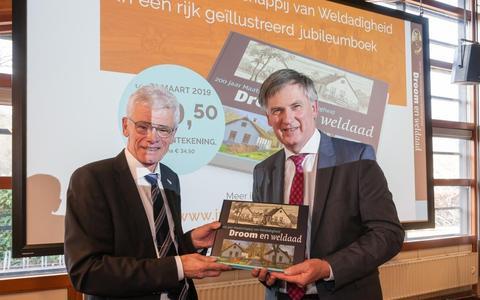Jan Mensink overhandigt het boek aan de Drentse gedeputeerde Cees Bijl.
