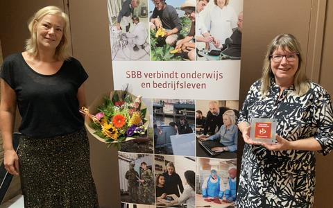 Linda Duitman overhandigt bloemen aan teammanager Anneke de Munnik.