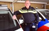 """Wijkagent Bertus de Groot tussen twee politievoertuigen. """"Zelf mag ik ook graag op de motor rijden."""""""