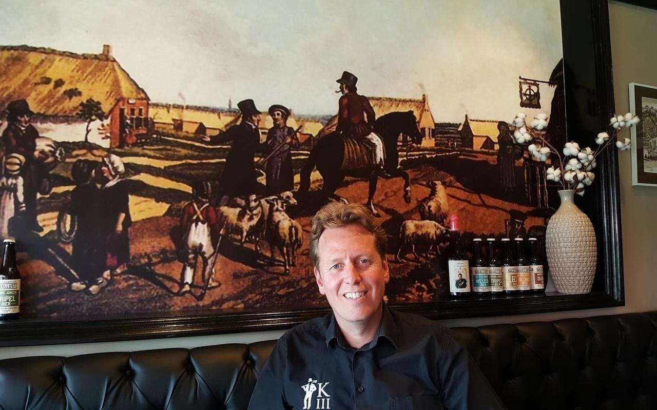 Arjan Stroeve in zijn café De Steen voor een schilderij met een tafereel uit de Kolonie van Weldadigheid van bijna twee eeuwen geleden.