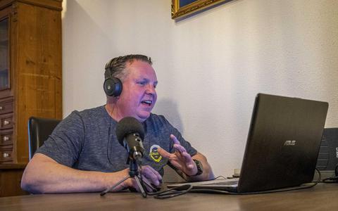 Marco Bisschop volgt de koorrepetities bij via zijn laptop.